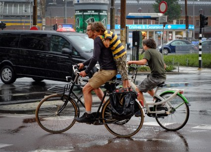 A boy gets a ride with a man on his bicycle in Amsterdam.