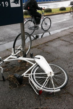 A white bike has fallen over while parked on the street in Amsterdam.