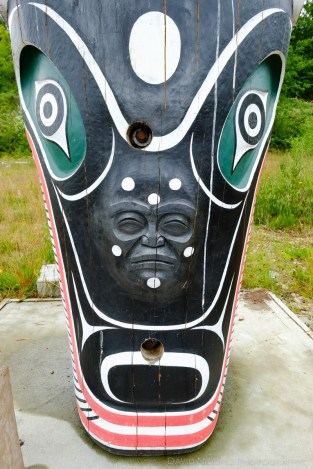 A figure peers from the base of a Totem Pole in Alert Bay, BC.