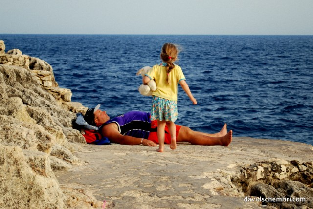 A girl approaches her father, who is trying to sunbathe. © All rights reserved David Schembri 2010