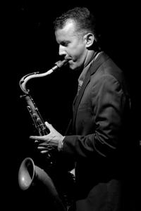 David Sills studio shot playing saxophone in black and white