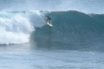 Photo of David Sills - Surfer-Saxophonist taking wide stance partway down a large wave