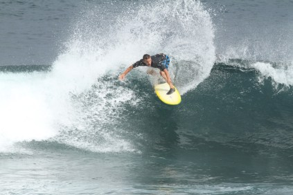 Photo of David Sills - Surfer-Saxophonist leaning low while riding the very crust of a wave