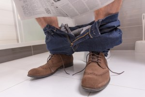 person sitting on the toilet reading a newspaper