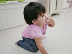 baby on floor putting foreign object in her mouth
