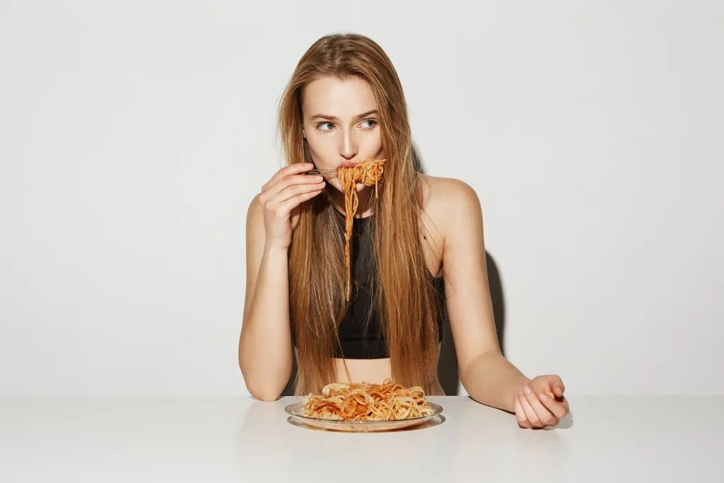young lady eating pasta