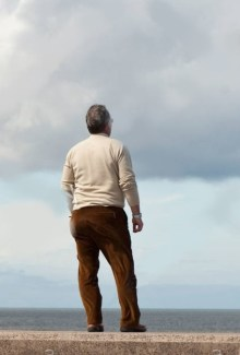 rear-view-of-a-man-standing-on-sea-wall-another-man-looking-through-BKKJJ5