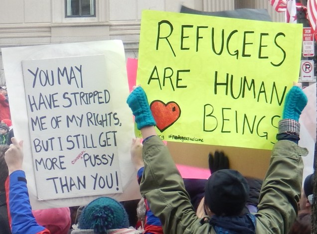 """Signs read """"You may have stripped me of my rights, but I still get more CONSENSUAL pussy than you!"""" and """"Refugees are human beings"""""""