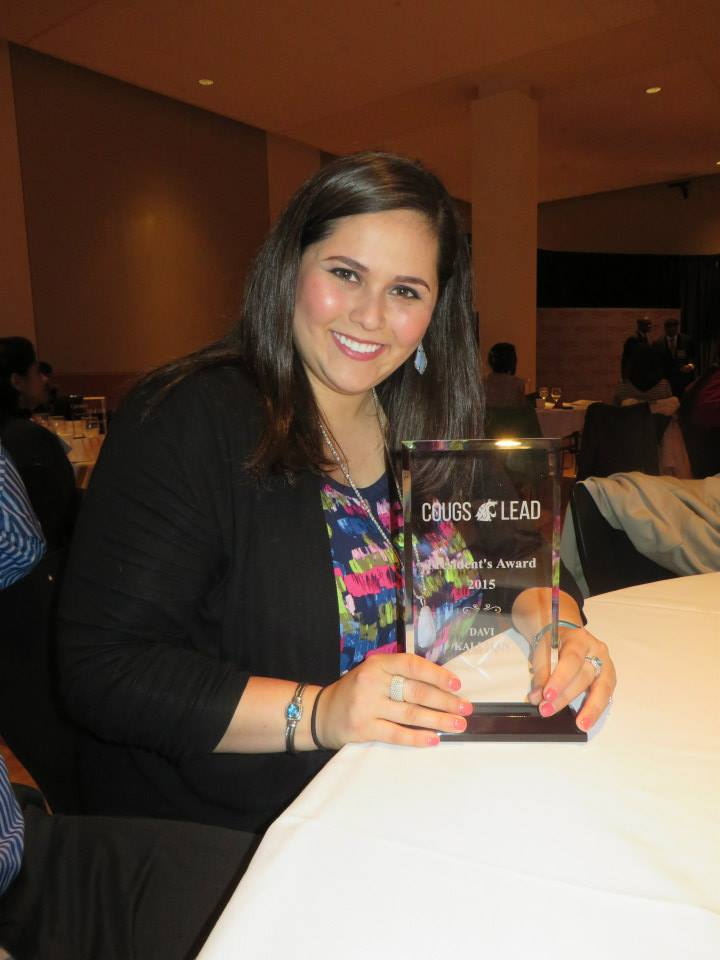 Photo of Davi holding up a Cougs Lead trophy. She is smiling at the camera and sitting at a table.