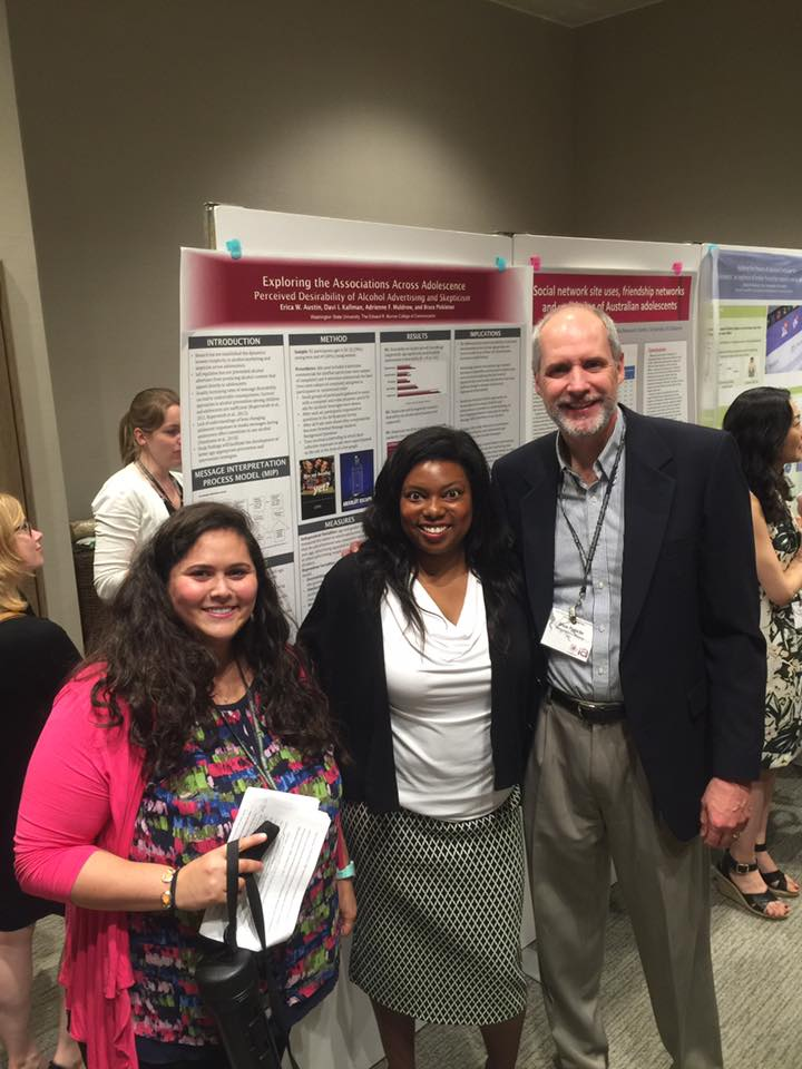 Photo of Davi, Adrienne, and Dean Pinkleton in front of a poster board smiling.