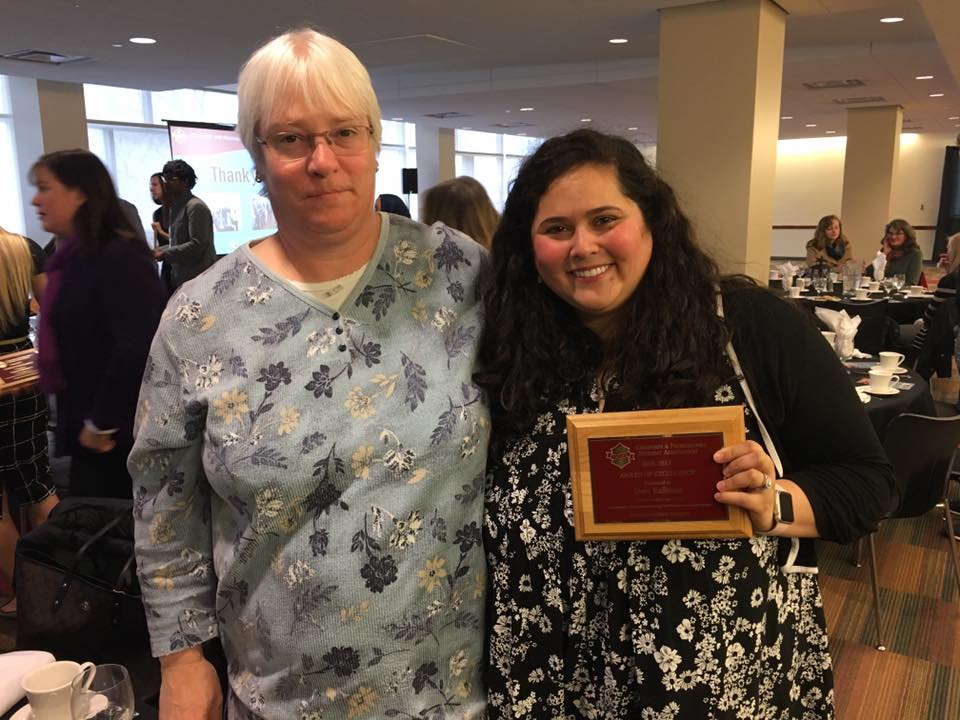 Photo of Dean Lisa Gloss hugging Davi as she holds up a GPSA plaque. They are both smiling and looking at the camera.
