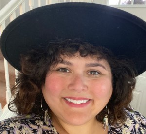 Davi is smiling at the camera. She has short brown curly hair and is wearing a wide brim black wool hat.