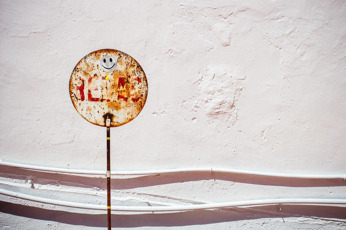 Rostiges rundes Schild mit Smiley-Aufkleber und verblasster roter Schrift vor weisser Wand