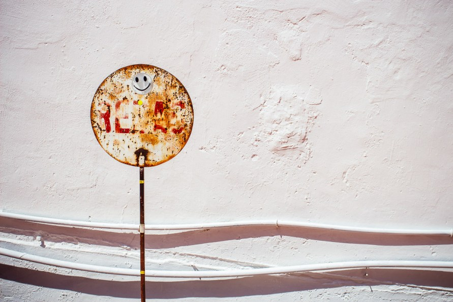 rusty round sign with smiley sticker in front of white wall