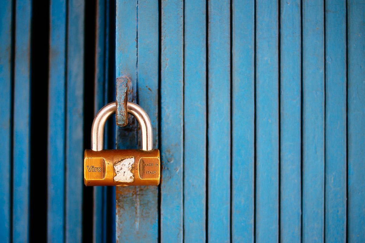 small golden lock on folded blue metal door