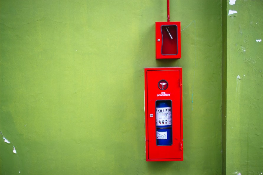 blue fire-extinguisher in red box installed on green wall