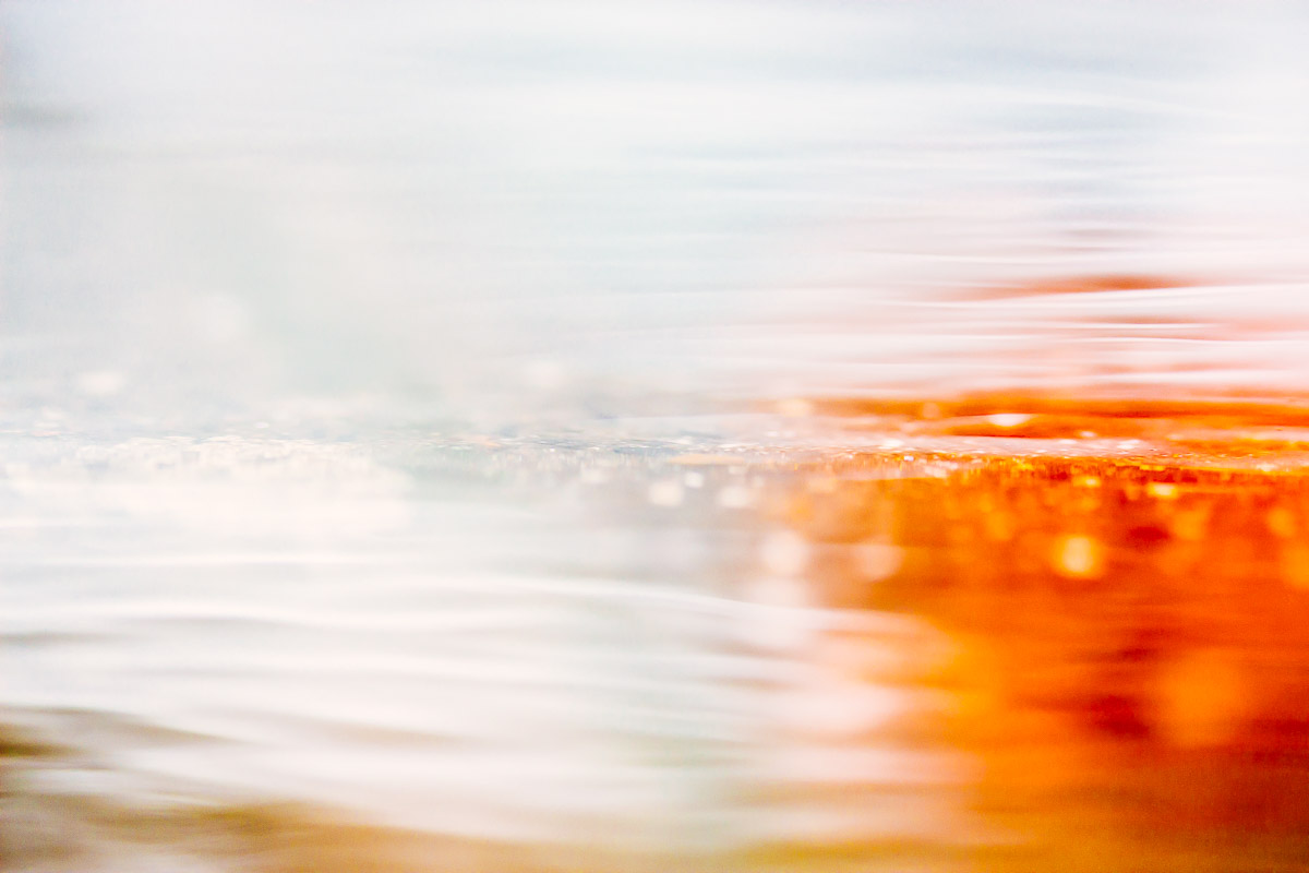 Abstract image of a puddle surface in shades of white, brown and orange