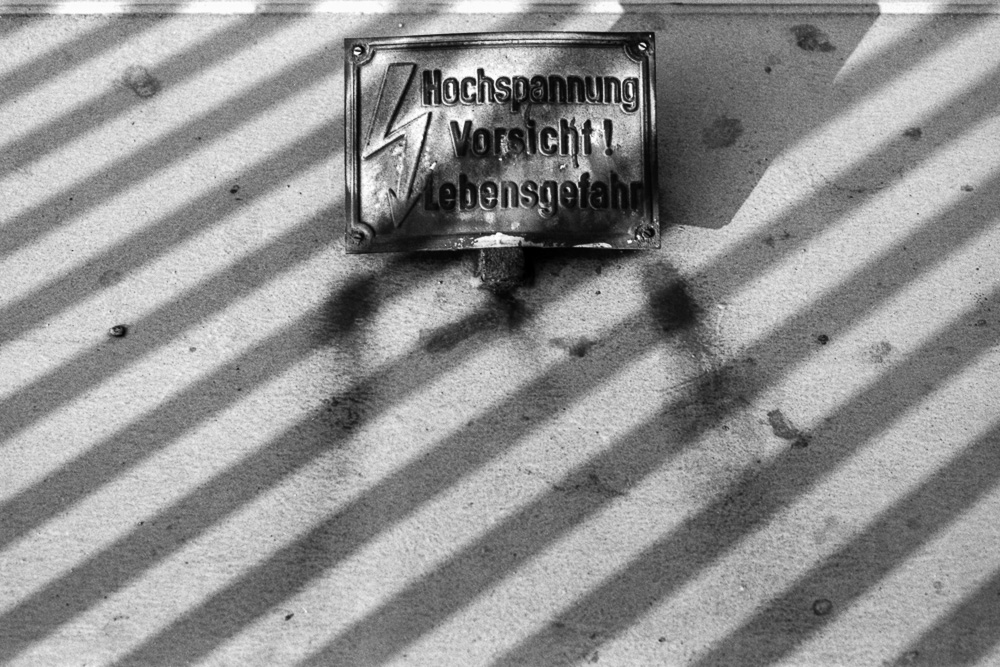 High voltage warning sign surrounded by stripy shadows on concrete wall