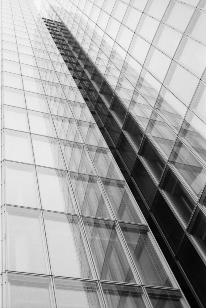 Monochrome image of a high office building with a glass front
