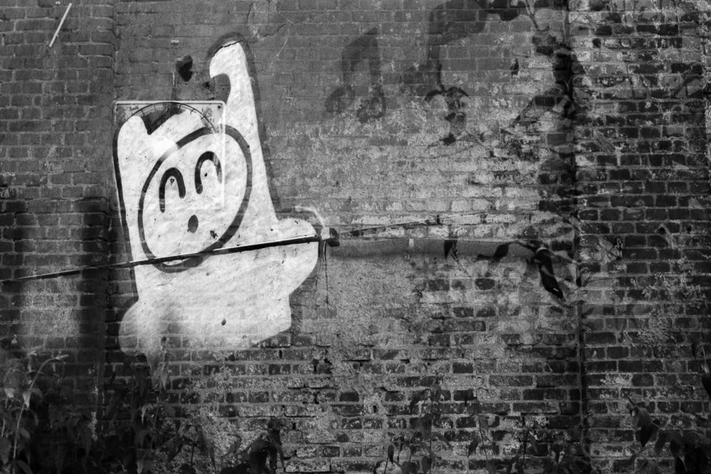 Doppelbelichtung eines Cartoon-Graffitis an einer alten Ziegelsteinmauer
