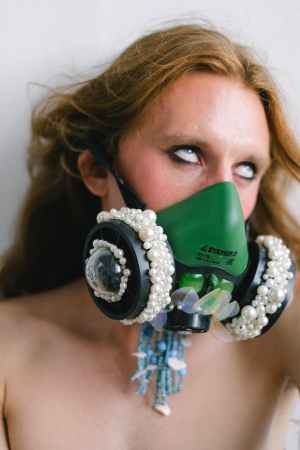 transsexual guy with long hair in trendy respirator mask