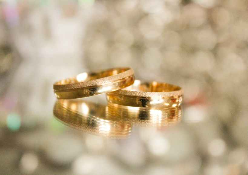 two gold colored rings in selective focus photography