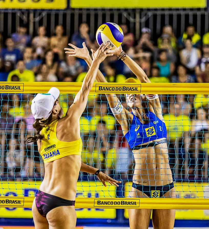 two woman playing volleyball