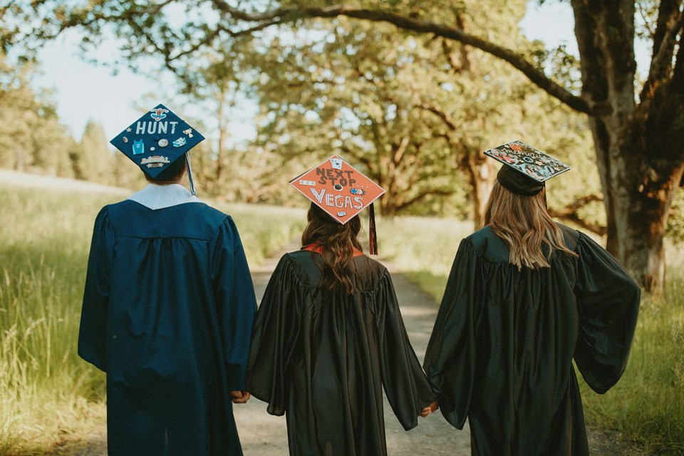 friends holding hands in their cap and gowns
