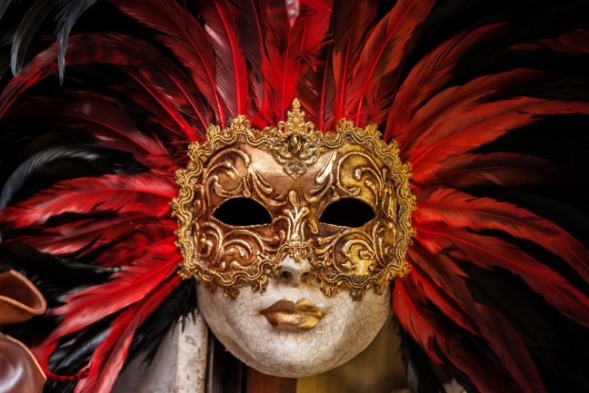 gold carnival mask with red feathered headdress