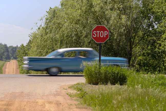 a blue classic car passing by