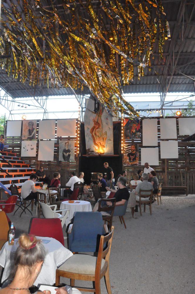 Im Festivalcafé spielt Livemusik. Dekoriert hat es Christopher Haley Simpson mit seinen Gemälden und einem Augenzwinkern: Eines der Bilder hängt aus aktuellem Anlass auf Baselitz anspielend verkehrt herum. Foto: Una Giesecke