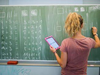Eine junge Lehrerin schreibt an eine Schultafel. Foto: Julian Stratenschulte/Archiv