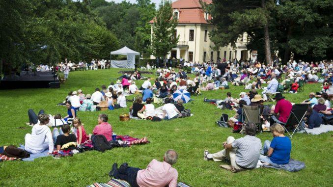 «Moritzburg Festival»-Besucher sitzen im Schlossgarten zusammen. Foto: Ole Spata/Archiv