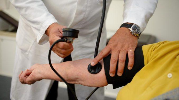 Ein Arzt misst einer Patientin den Blutdruck. Foto: Bernd Weissbrod/Archiv