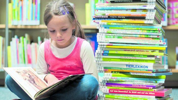 Ein kleines Mädchen liest - rund um den Welttag des Buches am 23. April gibt es in Schulen, Buchhandlungen und Bibliotheken eine Vielzahl an spannenden Aktionen. (Foto: Stiftung Lesen)