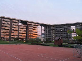 Meningen med livet? Bygningerne ligger som en firlænget gård omkring et område med boldbane og legeplads -