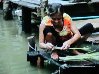 En Thailandsk kvinde ordner grøntsager ved en kanal