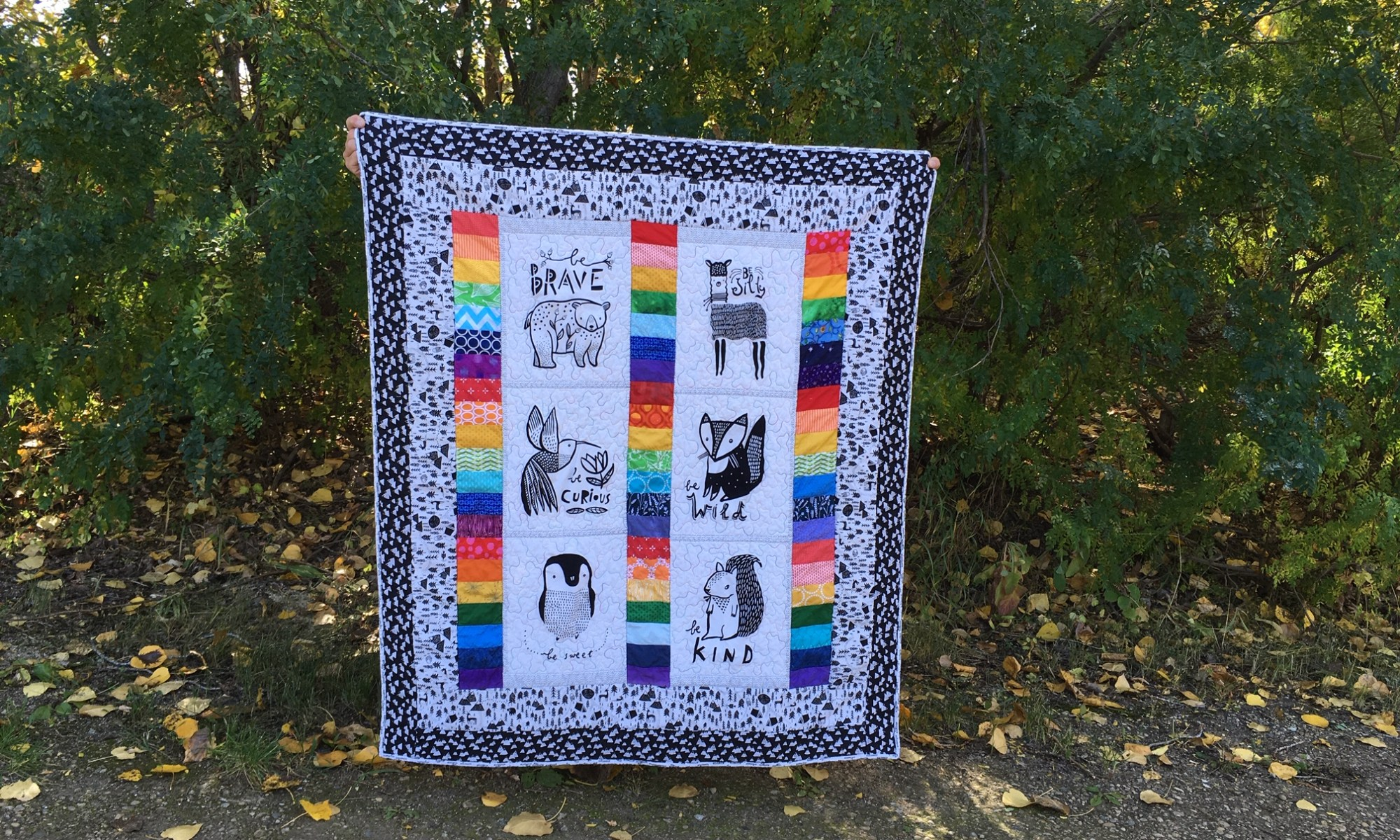 Black and white animals with rainbows child's quilt.