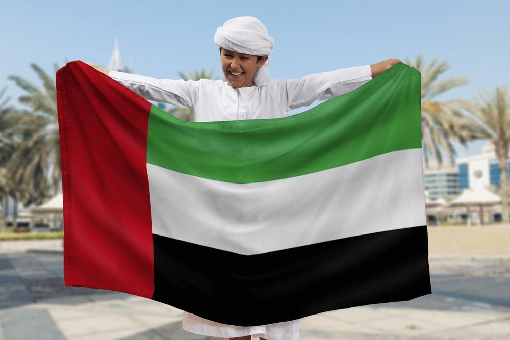 Arabian Boy Holding UAE Flag Outdoors
