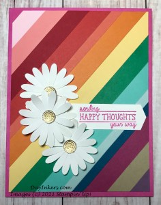 Hand crafted greeting card using scrap pieces to create a rainbow background for punched daisy clusters.