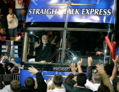 "McCain waves to supporters through the windshield of his ""Straight Talk Express"" during the 2000 presidential primary"