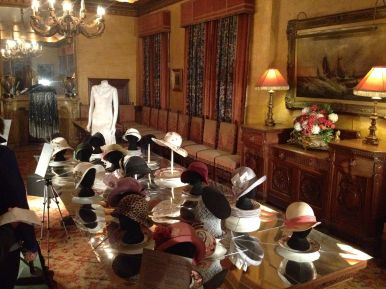 Hats displayed on dining table w white dress & cape
