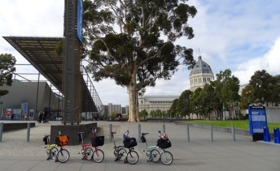 Bromptons in a line before the Melbourne Museum (left) and Royal Exhibition Building (right)