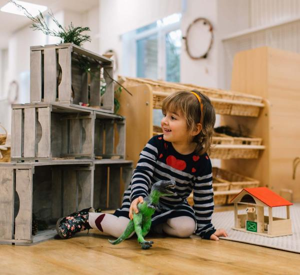 Child playing with toy dinosaur at the Maples Day Nursery