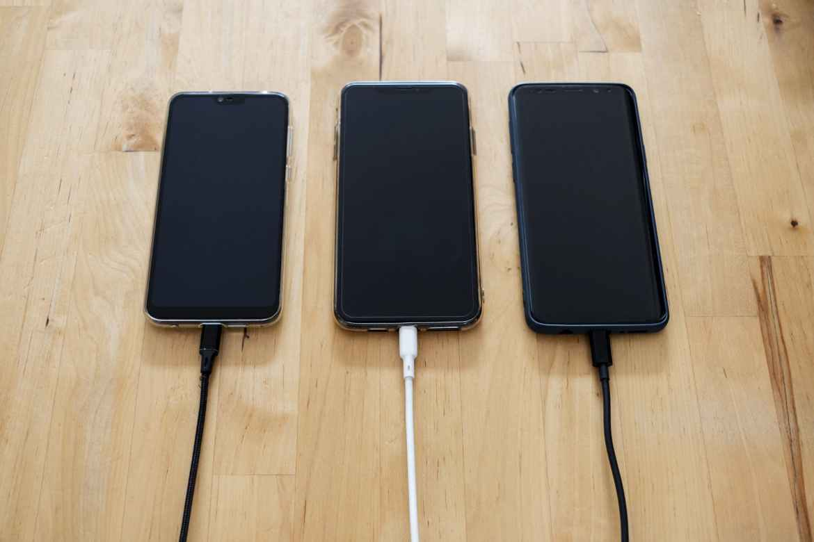 black android smartphones on brown wooden surface