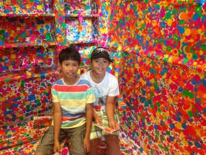 two boys inside a colorful room full of stickers
