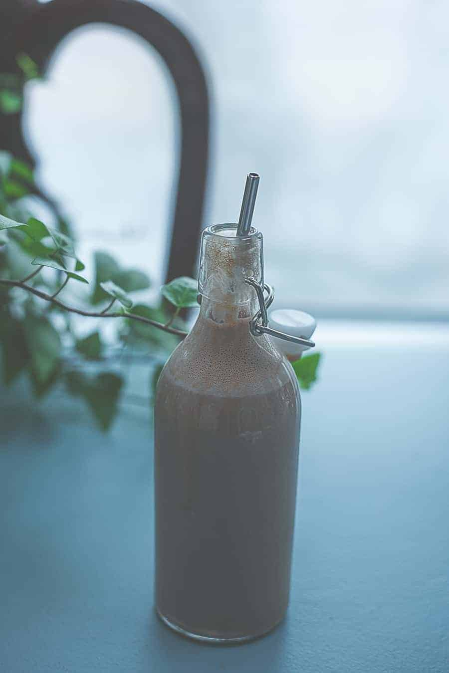 chocolate milk in glass bottle with stainless steel straw