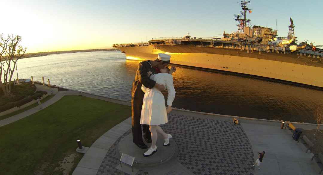 Sailor Kissing Nurse next to the USS Midway Museum at Sunset
