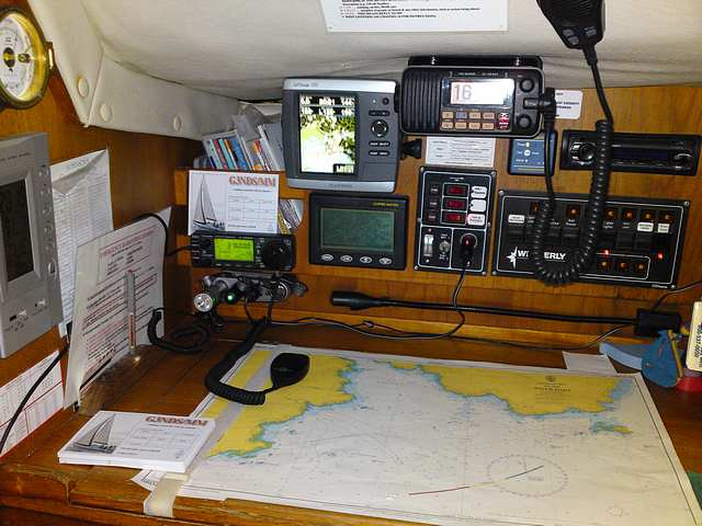 Christine Marie's navigation table.  IC706 Mk2G lower left, Marine VHF top.  GPS and Navtext left of VHF.