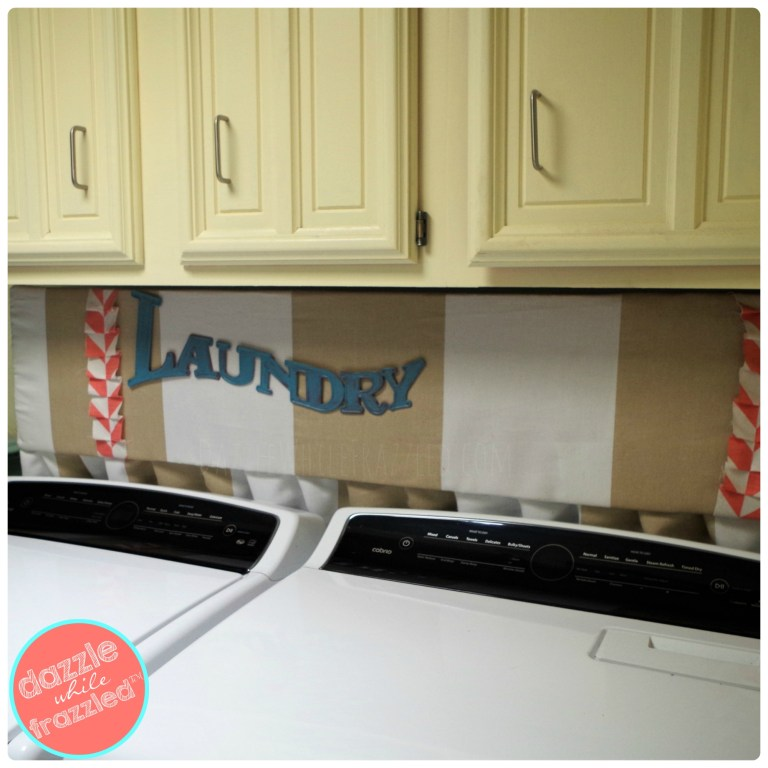 Install a DIY fabric-covered cork board in laundry room to hide laundry hook ups